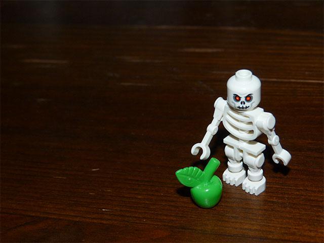 LEGO-Skelett und grüner Apfel